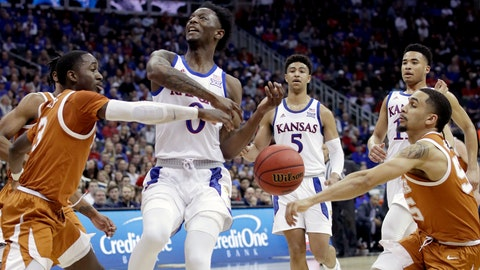 <p>               Texas' Courtney Ramey, left, and Kamaka Hepa, right, strip the ball from Kansas' Marcus Garrett (0) during the first half of an NCAA college basketball game in the Big 12 men's tournament Thursday, March 14, 2019, in Kansas City, Mo. (AP Photo/Charlie Riedel)             </p>