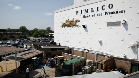 """<p>               FILE - In this May 15, 2018 file photo, people walk outside of a building at Pimlico Race Course as preparations take place for the Preakness Stakes horse race, in Baltimore. Baltimore has ratcheted up a bitter dispute with the owners of the historic racetrack in an effort to seize a nearly 150-year-old course and block the move of one of America's premier horse races out of the city where it was first run in 1873. Under state law, the Preakness Stakes - the middle jewel of the Triple Crown of thoroughbred horse racing - can be moved to another track in Maryland """"only as a result of a disaster or emergency."""" But the Canada-based development company that owns and operates the rundown Pimlico Race Course has made it abundantly clear that it wants to move the storied race out of the city. (AP Photo/Patrick Semansky, File)             </p>"""