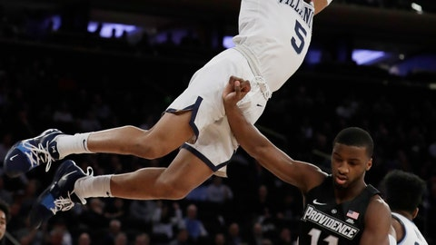<p>               Villanova's Phil Booth (5) hangs from the rim over Providence's Alpha Diallo (11) after after dunking the ball during the first half of an NCAA college basketball game in the Big East conference tournament, Thursday, March 14, 2019, in New York. (AP Photo/Frank Franklin II)             </p>