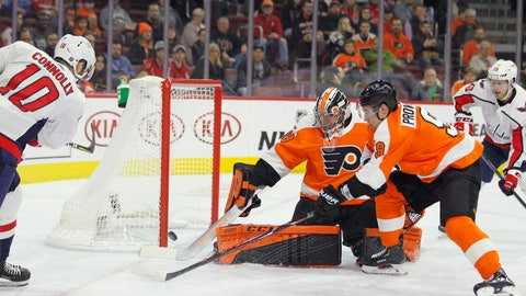<p>               Washington Capitals' Brett Connolly, left, scores past Philadelphia Flyers goalie Carter Hart, center, and Ivan Provorov, right, during the first period of an NHL hockey game Thursday, March 14, 2019, in Philadelphia. (AP Photo/Tom Mihalek)             </p>