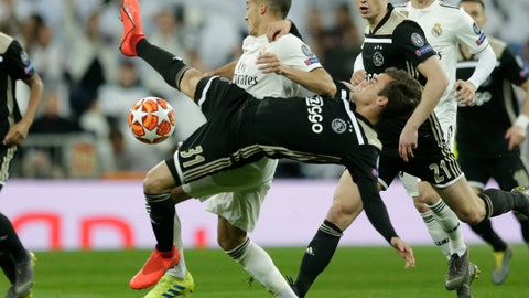<p>               Real forward Lucas Vazquez, background, and Ajax's Nicolas Tagliafico challenge for the ball during the Champions League soccer match between Real Madrid and Ajax at the Santiago Bernabeu stadium in Madrid, Spain, Tuesday, March 5, 2019. (AP Photo/Manu Fernandez)             </p>