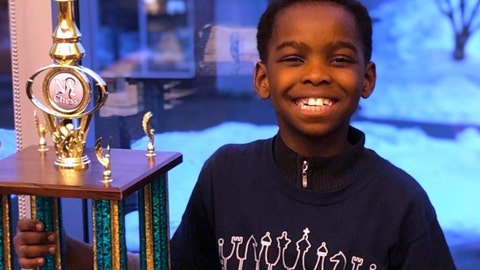 <p>               In this photo taken Sunday, March 10, 2019 in Saratoga, N.Y., 8-year-old Tanitoluwa Adewumi poses with his trophy after winning the New York State Scholastic Championships tournament for kindergarten through third grade. The victory will be his family's ticket out of a homeless shelter. Tani and his family have lived in a New York City shelter since fleeing Nigeria in 2017. (Russell Makofsky via AP)             </p>