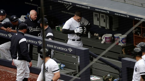 <p>               New York Yankees' Aaron Judge, center, clenches his helmet while walking in the dugout after he was pulled from the game after suffering an apparent injury while hitting a single off Kansas City Royals starting pitcher Glenn Sparkman during the sixth inning of a baseball game, Saturday, April 20, 2019, in New York. (AP Photo/Julio Cortez)             </p>