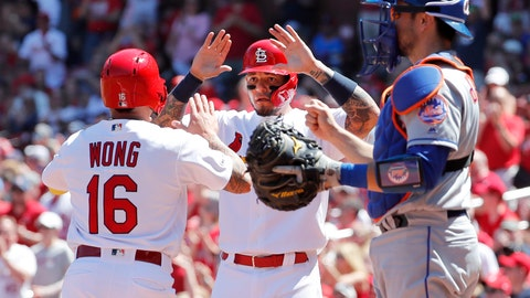 <p>               St. Louis Cardinals' Kolten Wong, left, and teammate Yadier Molina celebrate after scoring past New York Mets catcher Travis d'Arnaud, right, during the second inning of a baseball game Sunday, April 21, 2019, in St. Louis. (AP Photo/Jeff Roberson)             </p>