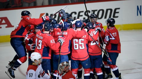 <p>               The Washington Capitals celebrate after overtime of Game 2 of an NHL hockey first-round playoff series as Carolina Hurricanes defenseman Trevor van Riemsdyk (57) and goaltender Petr Mrazek (34) skate by, Saturday, April 13, 2019, in Washington. The Capitals won 4-3 in overtime. (AP Photo/Nick Wass)             </p>