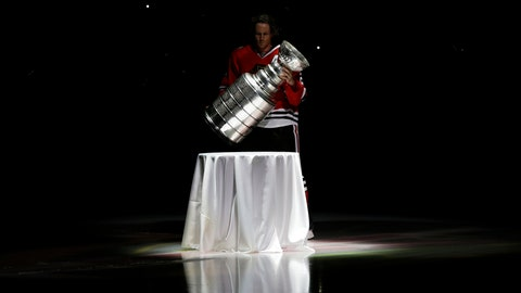 <p>               In this Oct. 1, 2013, photo, Chicago Blackhawks defenseman Duncan Keith carries out the Stanley Cup during a banner raising ceremony before an NHL hockey game between the Blackhawks and the Washington Capitals in Chicago. In an Associated Press and Canadian Press survey of player representatives from all 31 NHL teams, 48 percent favor changing the current divisional playoff format. (AP Photo/Nam Y. Huh)             </p>