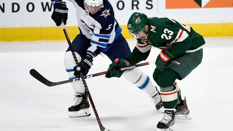 <p>               Winnipeg Jets defenseman Dmitry Kulikov (5), of Russia, passes away from Minnesota Wild right wing J.T. Brown (23) during the first period of an NHL hockey game, Tuesday, April 2, 2019, in St. Paul, Minn. (AP Photo/Hannah Foslien)             </p>