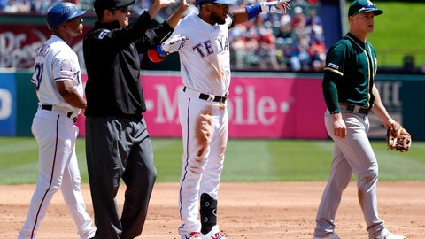 <p>               Texas Rangers' Elvis Andrus stands on third celebrating his run-scoring triple as base coach Tony Beasley, umpire Jansen Visconti and Oakland Athletics' Matt Chapman stand by in the first inning of a baseball game in Arlington, Texas, Sunday, April 14, 2019. The hit scored Delino DeShields. (AP Photo/Tony Gutierrez)             </p>