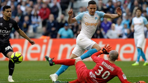 <p>               Marseille's Florian Thauvin, left, challenges for the ball with Nimes' goalkepper Paul Bernardoni, during the League One soccer match between Marseille and Nimes, at the Velodrome Stadium, in Marseille, southern France, Saturday, April 13, 2019. (AP Photo/Claude Paris)             </p>