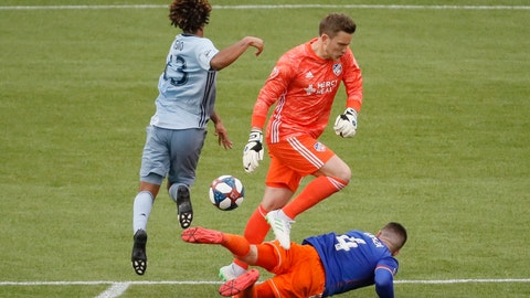 <p>               Sporting Kansas City forward Gianluca Busio, left, clears the ball from FC Cincinnati goalkeeper Spencer Richey and defender Greg Garza (4) before scoring on an open goal during the second half of an MLS soccer match Sunday, April 7, 2019, in Cincinnati. (AP Photo/John Minchillo)             </p>
