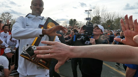 <p>               Mamadi Diakite hoods the NCAA championship trophy as Virginia team members are welcomed by fans as they return to Charlottesville, Va., Tuesday, April 9, 2019, the day after defeating Texas Tech in the title game of college basketball's Final Four. (AP Photo/Steve Helber)             </p>