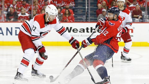 Apr 20, 2019; Washington, DC, USA; Washington Capitals center Evgeny Kuznetsov (92) shoots the puck as Carolina Hurricanes defenseman Brett Pesce (22) defends in the third period in game five of the first round of the 2019 Stanley Cup Playoffs at Capital One Arena. The Capitals won 6-0. Mandatory Credit: Geoff Burke-USA TODAY Sports
