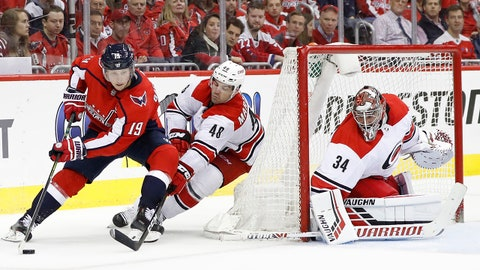 Apr 11, 2019; Washington, DC, USA; Washington Capitals center Nicklas Backstrom (19) skates with the puck behind Carolina Hurricanes goaltender Petr Mrazek (34) as Hurricanes left wing Jordan Martinook (48) chases in the third period in game one of the first round of the 2019 Stanley Cup Playoffs at Capital One Arena. The Capitals won 3-2. Mandatory Credit: Geoff Burke-USA TODAY Sports