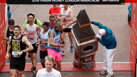 <p>               Lukas Bates wearing a costume of the Queen Elizabeth Tower (known as Big Ben) is helped by an official as he attempts to get past the finishing line, during the 39th London Marathon in London, Sunday, April 28, 2019. (AP Photo/Alastair Grant)             </p>