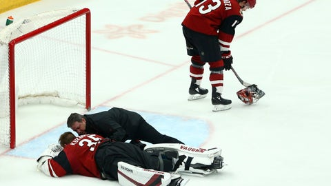 <p>               After getting a stick to the face, injured Arizona Coyotes goaltender Darcy Kuemper (35) is attended to by a team trainer as Coyotes center Vinnie Hinostroza (13) picks up Kuemper's mask during the third period of an NHL hockey game against the Los Angeles Kings, Tuesday, April 2, 2019, in Glendale, Ariz. The Kings defeated the Coyotes 3-1. (AP Photo/Ross D. Franklin)             </p>