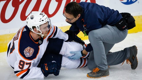 <p>               Edmonton Oilers' Connor McDavid has his knee tended too after crashing into Calgary Flames goalie Mike Smith during the second period of an NHL hockey game Saturday, April 6, 2019, in Calgary, Alberta. McDavid left the game. (Jeff McIntosh/The Canadian Press via AP)             </p>