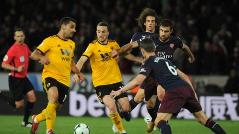 <p>               Wolverhampton's Diogo Jota, center, duels for the ball with Arsenal's Sokratis Papastathopoulos, right, during the English Premier League soccer match between Wolverhampton Wanderers and Arsenal at the Molineux Stadium in Wolverhampton, England, Wednesday, April 24, 2019. (AP Photo/Rui Vieira)             </p>