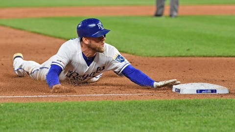 Kansas City Royals designated hitter Hunter Dozier (17) dives into third base after tripling in two runs during the fifth inning against the Los Angeles Angels at Kauffman Stadium.