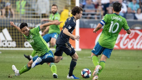 <p>               Philadelphia Union's Brenden Aaronson, center, slips between Seattle Sounders' Kim Kee-Hee, left, and Nicolas Lodeiro with the ball during the first half of an MLS soccer match Saturday, May 18, 2019, in Chester, Pa. (AP Photo/Chris Szagola)             </p>