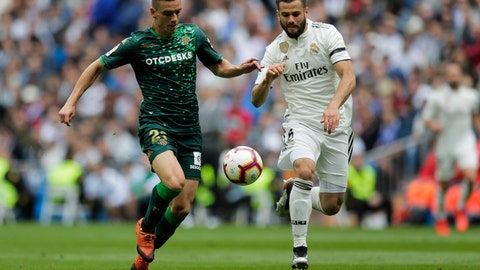 <p>               Betis player Lo Celso, left, duels for the ball against Real Madrid's Nacho Fernanzez during a Spanish La Liga soccer match at the Santiago Bernabeu stadium in Madrid, Spain, Sunday, May 19, 2019. (AP Photo/Bernat Armangue)             </p>
