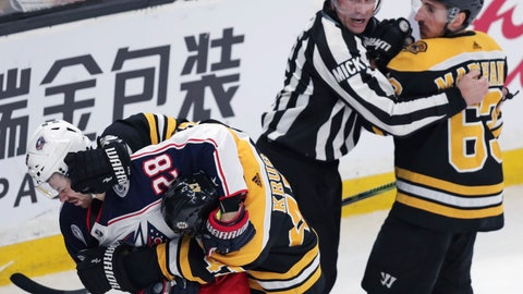 <p>               Columbus Blue Jackets right wing Oliver Bjorkstrand (28) and Boston Bruins defenseman Torey Krug tangle as linesman Mark Shewchyk holds back Bruins left wing Brad Marchand at the end of the first period of Game 2 of an NHL hockey second-round playoff series, Saturday, April 27, 2019, in Boston. (AP Photo/Charles Krupa)             </p>