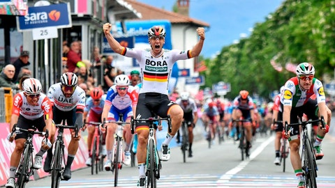 <p>               Germany's Pascal Ackermann, center, celebrates as he crosses the finish line to win the the 2nd stage of the Giro d'Italia, tour of Italy cycling race, from Bologna to Fucecchio, Sunday, May 12, 2019. (Alessandro Di Meo/ANSA via AP)             </p>