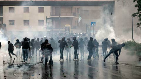 <p>               Lazio fans clash with police prior to the Italian Cup final soccer match between Lazio and Atalanta, in Rome, Wednesday, May 15, 2019. A police car was set on fire as Lazio fans clashed with local authorities near the Stadio Olimpico before the Italian Cup final on Wednesday. Italian national news agency Ansa reported that the two policemen who were in the car at the time have been taken to hospital for smoke inhalation, while one also had an injury to his ear. Lazio fans have also been throwing bottles, stones and other objects. (Massimo Percossi/ANSA via AP)             </p>