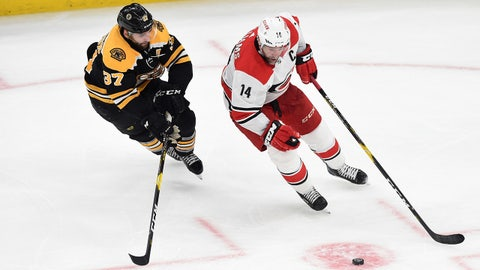 May 9, 2019; Boston, MA, USA; Carolina Hurricanes right wing Justin Williams (14) skates with the puck as Boston Bruins center Patrice Bergeron (37) defends during the third period in game one of the Eastern Conference Final of the 2019 Stanley Cup Playoffs at TD Garden. Mandatory Credit: Bob DeChiara-USA TODAY Sports