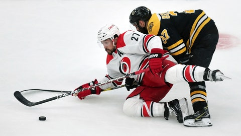 <p>               Carolina Hurricanes' Justin Faulk (27) tries to control the puck as he is dropped to the ice by Boston Bruins' Patrice Bergeron, right, during the first period in Game 2 of the NHL hockey Stanley Cup Eastern Conference final series, Sunday, May 12, 2019, in Boston. (AP Photo/Charles Krupa)             </p>