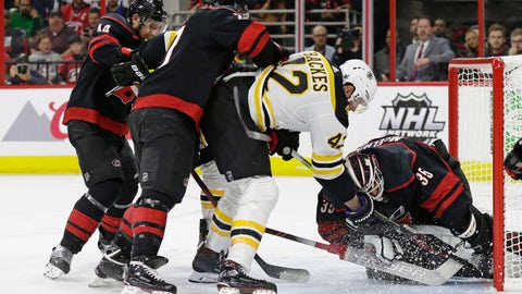 <p>               Boston Bruins' David Backes (42) tries to score against Carolina Hurricanes goalie Curtis McElhinney (35) while Hurricanes' Calvin de Haan (44) and Justin Faulk defend during the first period in Game 3 of the NHL hockey Stanley Cup Eastern Conference final series in Raleigh, N.C., Tuesday, May 14, 2019. (AP Photo/Gerry Broome)             </p>