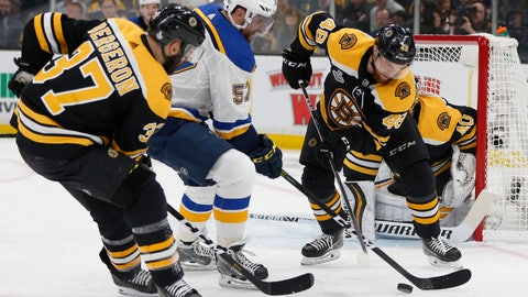 <p>               St. Louis Blues' David Perron (57) tries to move the puck between Boston Bruins' Patrice Bergeron (37) and Matt Grzelcyk (48) during the first period in Game 1 of the NHL hockey Stanley Cup Final, Monday, May 27, 2019, in Boston. (AP Photo/Michael Dwyer)             </p>
