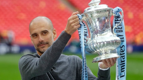 <p>               Manchester City's manager Pep Guardiola poses with the trophy after the English FA Cup Final soccer match between Manchester City and Watford at Wembley stadium in London, Saturday, May 18, 2019. (AP Photo/Kirsty Wigglesworth)             </p>