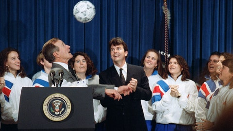 "<p>               FILE - In this Jan. 23, 1992, file photo, U.S. President George H. Bush heads a soccer ball while meeting the 1991 Women's World Cup soccer champions, in Washington. Anson Dorrance, coach of the team is at center. The 1999 and 2015 U.S. Women's World Cup teams have received plenty of attention and accolades over the years, but not much has been reported about the 1991 team that won the first Women's World Cup. ""Sports Illustrated's"" Grant Wahl is hoping to change that. The magazine is debuting a new podcast called ""Throwback"" with the first season focused on how the Women's World Cup started.(AP Photo/Barry Thumma, File)             </p>"