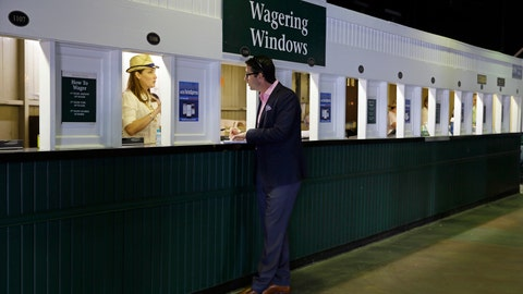 <p>               FILE - In this May 2, 2015, file photo, a man places a bet before the 141st running of the Kentucky Derby horse race at Churchill Downs, in Louisville, Ky. Picking a horse to win the Kentucky Derby is easy. Hoping that choice wins and pays off with a profit is the challenge.(AP Photo/Jeff Roberson, File)             </p>