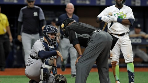 <p>               Home plate umpire Laz Diaz, center, talks to New York Yankees catcher Gary Sanchez, left, after he was hit on the head on a swing by Tampa Bay Rays' Guillermo Heredia, right, during the eighth inning of a baseball game Saturday, May 11, 2019, in St. Petersburg, Fla. Sanchez stayed in the game. (AP Photo/Chris O'Meara)             </p>