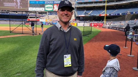 "<p>               Michigan football coach Jim Harbaugh and his son, Jack, stand on the field at Yankee Stadium before the New York Yankees' baseball game against the Tampa Bay Rays on Friday, May 17, 2019, in New York. Shaking hands and posing for photos on the field during batting practice, Harbaugh wore a Yankees cap, a Michigan sweater vest and — of course — a crisp pair of khakis. He says he and his father had never been to Yankee Stadium before and it's a ""bucket list"" trip for them. Harbaugh, a lifelong baseball fan, grew up rooting for the Detroit Tigers while his father was an assistant coach under Bo Schembechler at Michigan. (AP Photo/Mike Fitzpatrick)             </p>"
