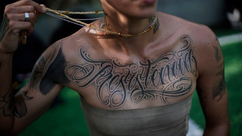 """<p>               In this May 13, 2019 photo, transgender Caua Fraga, 23, shows the tattoo on his chest that reads in Portuguese """"Resistance"""", before a training session with the Bigtboys transgender men's football team in Rio de Janeiro, Brazil. For the two dozen Bigtboys players, the training pitch is also one of the few places where they feel at ease and can talk about their experiences, good and bad, without fear. (AP Photo/Silvia Izquierdo)             </p>"""