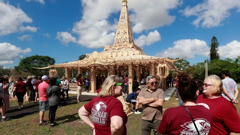 """<p>               FILE - In this Feb. 14, 2019, file photo, people gather around the """"Temple of Time"""" in honor of the 17 that were killed during the Marjory Stoneman Douglas High School shooting in 2018 in Coral Springs, Fla. The temple built as a memorial to the 17 victims of a Florida high school mass shooting is to be burned to the ground in a symbolic gesture of healing. (AP Photo/Wilfredo Lee, File)             </p>"""