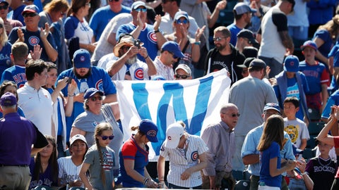 <p>               Fans hoist the flag to signify a victory for the Chicago Cubs, after the team's baseball game against the Colorado Rockies on Wednesday, June 12, 2019, in Denver. The Cubs won 10-1. (AP Photo/David Zalubowski)             </p>
