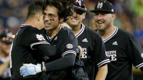 <p>               Mississippi State's Marshall Gilbert, second from left, is hugged by teammates after he drove in the winning run against Auburn in the ninth inning of an NCAA College World Series baseball game in Omaha, Neb., Sunday, June 16, 2019. Mississippi State won 5-4. (AP Photo/Nati Harnik)             </p>