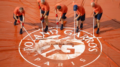 <p>               Stadium workers remove water from the court cover after rain interrupted quarterfinal matches of the French Open tennis tournament at the Roland Garros stadium in Paris, Tuesday, June 4, 2019. (AP Photo/Jean-Francois Badias)             </p>