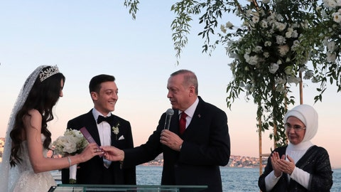 <p>               Turkey's President Recep Tayyip Erdogan speaks to Turkish-German soccer player Mesut Ozil and his wife Amine Gulse during a wedding ceremony over the Bosporus in Istanbul, Friday, June 7, 2019. Erdogan's wife Emine Erdogan is at right. (Presidential Press Service via AP, Pool)             </p>