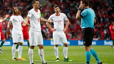 <p>               Switzerland's Granit Xhaka, second left, argues with referee Felix Brych, right, as he checking a VAR during the UEFA Nations League semifinal soccer match between Portugal and Switzerland at the Dragao stadium in Porto, Portugal, Wednesday, June 5, 2019. (AP Photo/Armando Franca)             </p>