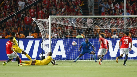 <p>               Egypt's Mahmoud Hassan, left, scores during the group A soccer match between Egypt and Zimbabwe at the Africa Cup of Nations at Cairo International Stadium in Cairo, Egypt, Friday, June 21, 2019. Egypt won 1-0. (AP Photo/Ariel Schalit)             </p>