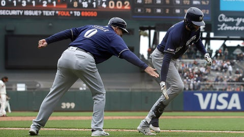 Milwaukee Brewers' Christian Yelich, right, is congratulated by third base coach Ed Sedar (0) after hitting a solo home run against the San Francisco Giants during the ninth inning of a baseball game in San Francisco, Saturday, June 15, 2019. (AP Photo/Jeff Chiu)