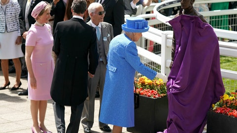 <p>               Britain's Queen Elizabeth II unveils a statue of famed jockey Lester Piggott, as Lester Piggott, front 3rd left, looks on with Sophie Countess of Wessex, left, during Derby Day at Epsom Racecourse, England, Saturday June 1, 2019. (John Walton/PA via AP)             </p>