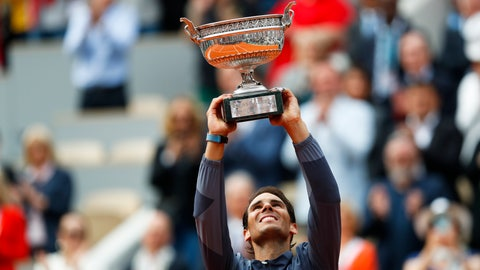 <p>               Spain's Rafael Nadal lifts the trophy as he celebrates his record 12th French Open tennis tournament title after winning his men's final match against Austria's Dominic Thiem in four sets, 6-3, 5-7, 6-1, 6-1, at the Roland Garros stadium in Paris, Sunday, June 9, 2019. (AP Photo/Pavel Golovkin)             </p>