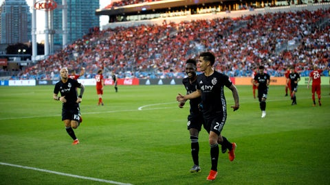 Sporting Kansas City midfielder Felipe Gutierrez (21) and forward Gerso (12) celebrate Gutierrez's goal against Toronto FC during the second half of an MLS soccer match Friday, June 7, 2019, in Toronto. (Cole Burston/The Canadian Press via AP)