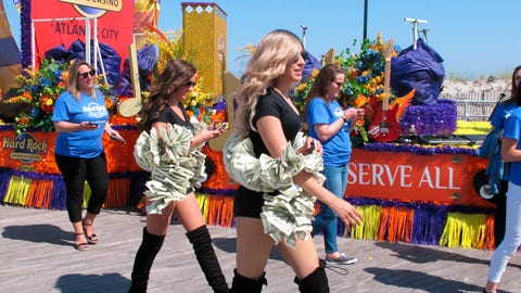 """<p>               This June 28, 2019 photo shows """"money girls"""" walking alongside a float for the Hard Rock casino in Atlantic City N.J. a year after it opened. Extra money from sports betting helped New Jersey's casinos and racetracks win nearly $284 million in June, up 21.5 percent from a year ago. (AP Photo/Wayne Parry)             </p>"""