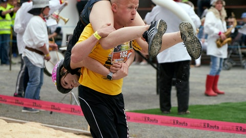 """<p>               People take part in the wife carrying race, a 278-yard obstacle course, during the 24th world championships in Sonkajarvi, Finland, Saturday, July 6, 2019. Despite the event's name couples don't have to be married, and organizers say male contestants could """"steal a neighbor's wife"""" if they didn't have a female companion. (AP Photo/David Keyton)             </p>"""